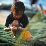 A boy helps tend the net of a local fisher (Photo by OECD)
