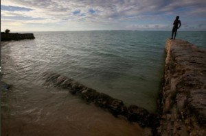 A boy stands on top of a seawall near the village of Tangintebu on South Tarawa in the central Pacific island nation of Kiribati May 26, 2013. (Photo from: REUTERS/David Gray/File Photo)